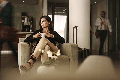 A female business executive sits in an airport lounge thoughtfully sipping coffee
