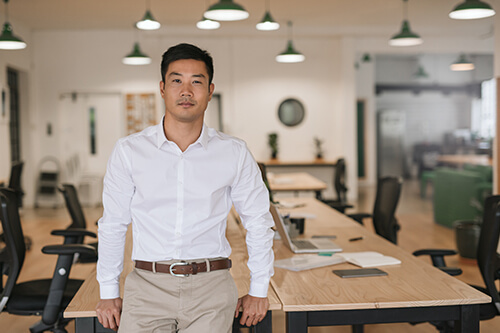 A young Asian-American business leader sits confidently on the edge of a table in an open office.