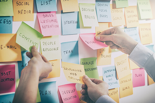 Hands arrange and rearrange multi-colored sticky notes on a white wall.