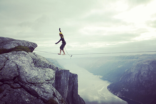 A tightrope walker balances on a wire crossing a deep mountain chasm high above a river.